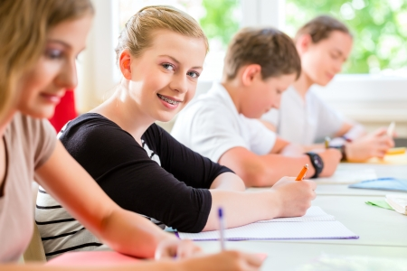 Studenti o alunni della scuola di classe impegnati in un programma della prova d'esame in aula concentrarsi sul loro lavoro