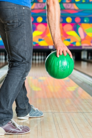 bowling pin: Young man in bowling alley having fun, the sporty man holding a bowling ball in front of the ten pin alley
