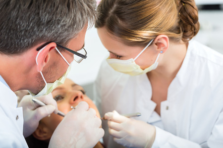 dental practice: Female patient with dentist and assistant in a dental treatment, wearing masks and gloves
