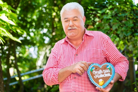 gingerbread heart: Senior in traditional Bavarian clothes or tracht with lederhosen and gingerbread souvenir heart in beergarden on Oktoberfest
