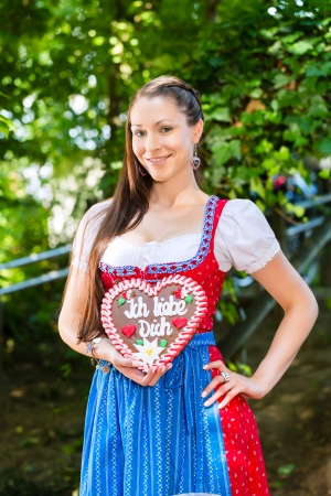 Young woman in traditional Bavarian clothes or tracht with a gingerbread souvenir heart in beergarden on Oktoberfest Stock Photo - 22401356