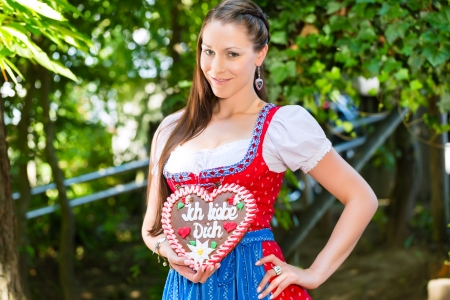 Young woman in traditional Bavarian clothes or tracht with a gingerbread souvenir heart in beergarden on Oktoberfest photo