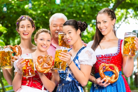 In Beer garden - friends, man and women in Tracht, Dirndl and Lederhosen drinking a fresh beer in Bavaria, Germany Stock Photo - 22401366