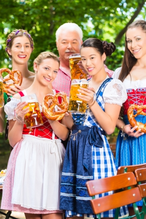 lederhosen: In Beer garden - friends, man and women in Tracht, Dirndl and Lederhosen drinking a fresh beer in Bavaria, Germany