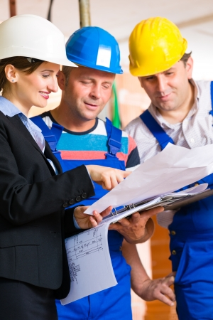 house worker: Construction site team or architect and builder or worker with helmets controlling or having discussion of plan or blueprint Stock Photo