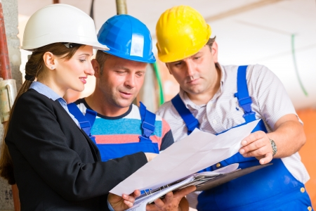 construction safety: Construction site team or architect and builder or worker with helmets controlling or having discussion of plan or blueprint Stock Photo