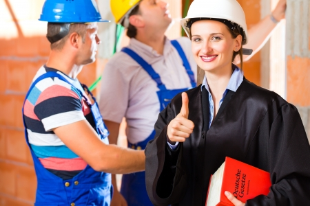 house inspection: Reviewer or expert or lawyer and builder or worker with helmets controlling a construction or building site to report defect or fault or deficiency in a protocol Stock Photo