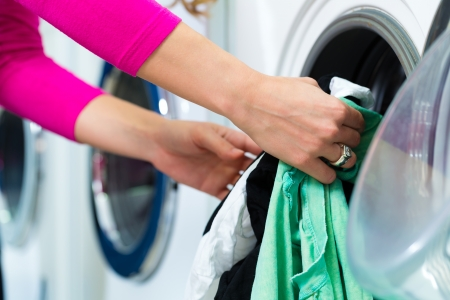 launderette: Young woman in a launderette, washing her dirty laundry, in the background are washing machines