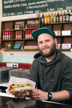 casse-cro�te: Hotdog - vendeur amical et client dans un rapide casse-cro�te de nourriture Banque d'images