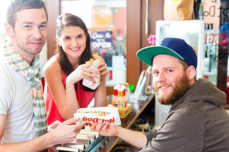 casse-cro�te: Hotdog - jeunes clients dans un snack-bar manger de d�licieuses saucisses de fast-food