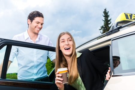 Young businesswoman gets out of taxi, she holding a cup of coffee photo