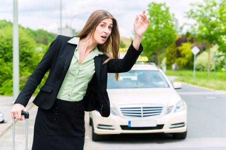 Young businesswoman waiting for a taxi stopping the driver waving from the sidewalk photo