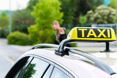 Jonge zakenvrouw te wachten op een taxi stoppen van de bestuurder zwaaien vanaf de stoep