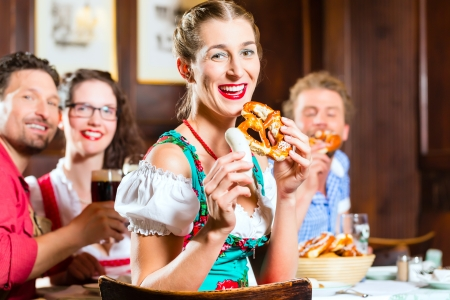 tracht: Young people in traditional Bavarian Tracht eating with sausages in restaurant or pub lunch or dinner