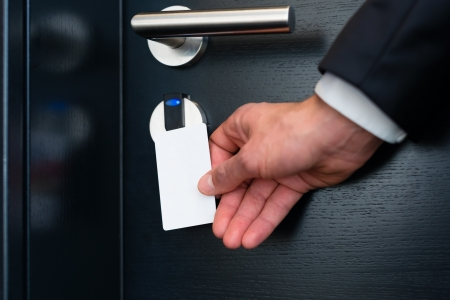 Hotel door - Young man holding a keycard in front of the electronic sensor of a room door  photo