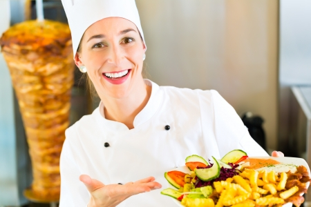 eatery: Doner kebab - friendly female vendor in a Turkish fast food eatery, holding plate with fries and kebab in front of skewer