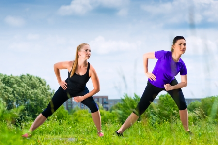 greenfield: Urban sports - young women doing warming up together before running in the greenfield on a summer day Stock Photo