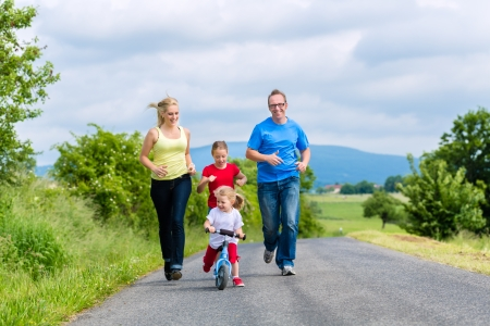 Family of Little girl father and mother or mom and dad running on street in rural environment for sport photo