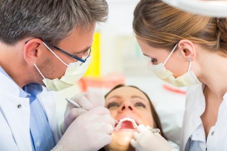 dentista: Paciente de sexo femenino con el dentista y asistente en un tratamiento dental, m?scaras y guantes