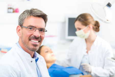 male dentist: Dentists in his surgery looking at the viewer, in the background his assistant is giving a female patient a treatment