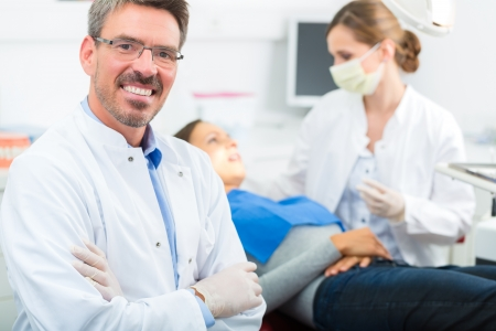 Dentists in his surgery looking at the viewer, in the background his assistant is giving a female patient a treatment
