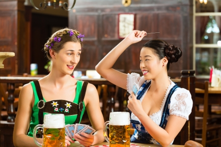 In Pub - friends in Tracht, Dirndl and Lederhosen drinking a fresh beer in Bavaria, Germany playing cards Stock Photo - 22797032
