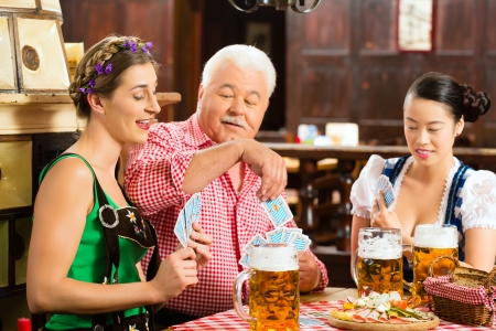 tracht: In Pub - friends in Tracht, Dirndl and Lederhosen drinking a fresh beer in Bavaria, Germany playing cards