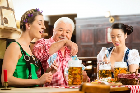 In Pub - friends in Tracht, Dirndl and Lederhosen drinking a fresh beer in Bavaria, Germany playing cards Stock Photo - 22797034