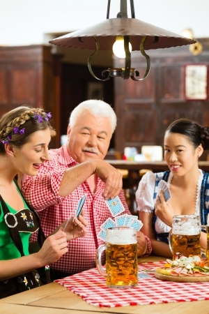 skat: In Pub - friends in Tracht, Dirndl and Lederhosen drinking a fresh beer in Bavaria, Germany playing cards