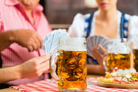 In Pub - friends in Tracht, Dirndl and Lederhosen drinking a fresh beer in Bavaria, Germany playing cards Stock Photo - 22797056