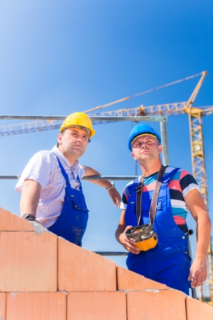 Two proud construction site workers or bricklayers standing on house project directing the crane with a remote control photo