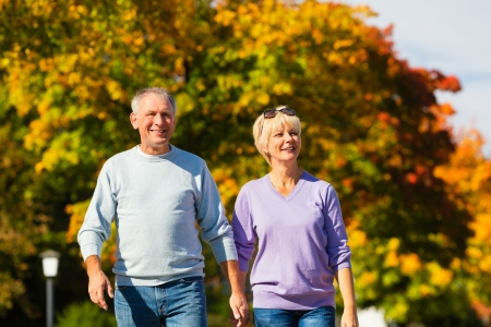 intimacy: senior couple, Man and woman, having a walk in autumn or fall outdoors, the trees show colorful foliage