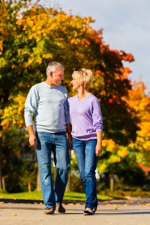 old people walking: senior couple, Man and woman, having a walk in autumn or fall outdoors, the trees show colorful foliage