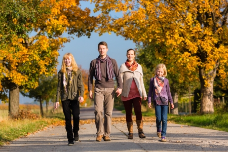 Young family with Mother, father and daughters walking through colorful trees in fall or autumn photo