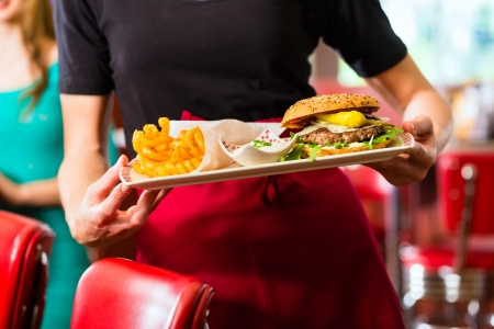 Friends or couple eating fast food with burger and fries in American fast food diner photo