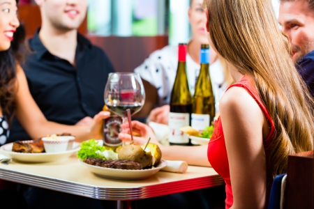 restaurant people: Friends or couples eating fast food and drinking beer and wine in a American fast food diner