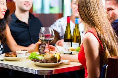 eten: Vrienden of koppels eten van fast food en het drinken van bier en wijn in een Amerikaanse fast food diner