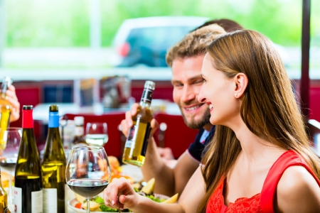Friends or couples eating fast food and drinking beer in a American fast food diner photo