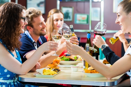 diners: Friends or couples eating fast food and drinking beer and wine in a American fast food diner