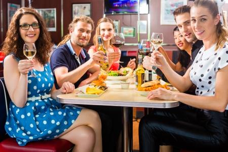 Amigos o parejas que comen el alimento y la bebida rápida cerveza y el vino en un restaurante de comida rápida americana