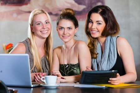 Young women or colleagues working in a cafe or restaurant, on some documents or contract with Laptop and Tablet Computer Stock Photo - 22880310