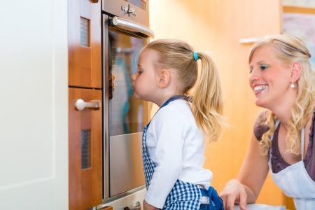 Mother and daughter baking cookies or cooking in the oven at home Stock Photo - 22880326