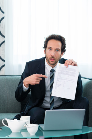 Businessman working in the hotel, on a contract or document and is confused about it photo