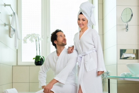 woman in towel: Young couple in bathroom of hotel making a bubble bath
