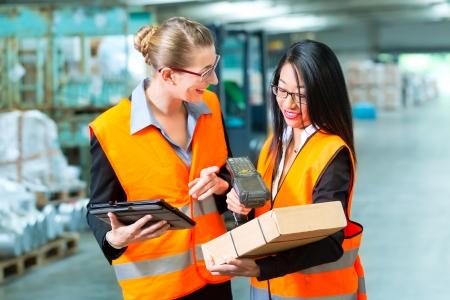 物流 - 女性労働者または荷送人と従業員や同僚、防弾チョッキとスキャナー、貨物輸送会社の倉庫に立って彼はパッケージのバーコードをスキャン 写真素材