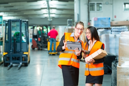 barcode scanner: Logistics - female worker or shipper and employee or colleagues, with protective vest and scanner, scans bar-code of package, he standing at warehouse of freight forwarding company