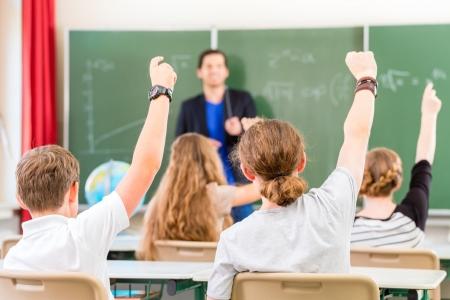 学校教師を与える授業、黒板またはボード指導学生や生徒の前で、彼らが手を上げて彼らはすべての答えを知っているように