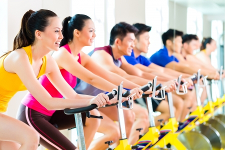 asian sport: Chinese Asian sport group of men and women in fitness club or gym exercising on spinning bikes