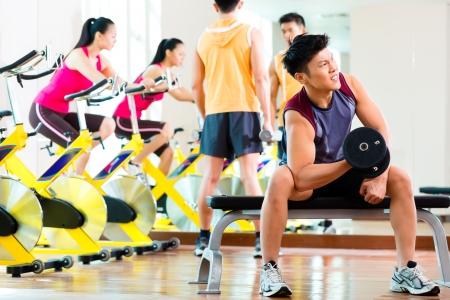woman fitness: Groupe asiatique chinois d'hommes et de femme faire de l'exercice ou de la formation sportive en salle de fitness avec des poids d'halt�res pour plus de puissance