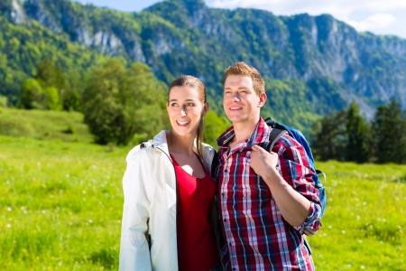 Happy couple walking on the grass in front of mountain panorama photo